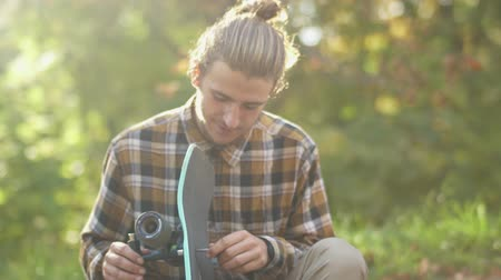 longboarding : Portrait of a young smiling guy in a plaid shirt customizing a skateboard. Young man with a skateboard outdoors. Stock Footage