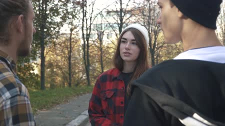 longboarding : Friends chatting outdoors. The girl in the white hat and plaid shirt talking to two guys in the park. Stock Footage