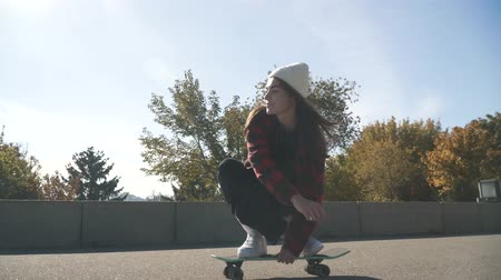 longboarding : Skateboarder girl in a white hat and a plaid shirt rides a skateboard outdoors. Hipster girl skateboarding in the park. Cute teen girl riding skate board. Hobbies and lifestyle.