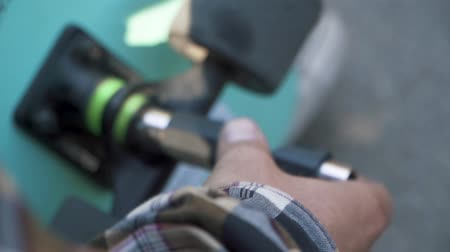 longboarding : Closeup of male hand fixing a skateboard. Cross-key for wheels.