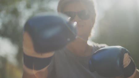 feminist : Portrait of adult woman shows punching moves in gloves on camera closeup. Female is happy and smiling. Slow motion.