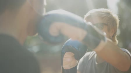 feminist : Adult woman in boxing gloves striking a man on the face. close up. Female in black sunglasses is happy and smiling.