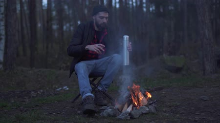 ivászat : Bearded man sit in the forest near bonfire and put beverage in a cup from vacuum flask . Brutal unshaven guy resting by the fire in the forest.