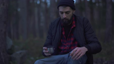 ivászat : Young bearded man sit in the forest near bonfire and put beverage in a cup from vacuum flask and drink. Brutal unshaven guy resting by the fire in the forest.
