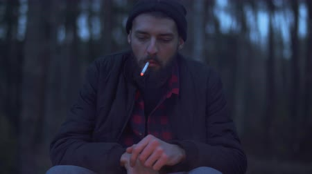 não barbeado : Bearded guy sitting by the fire in the forest begin to smoke. Brutal unshaven guy resting by the fire in the forest.