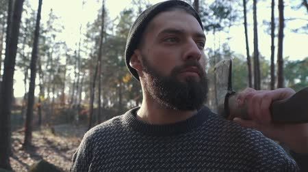 топор : Brutal bearded man with an axe on his shoulder looking far ahead. Unshaven guy with an ax in the forest. Стоковые видеозаписи