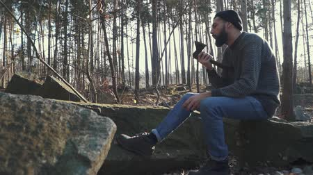 machado : Bearded guy sharps an axe in the forest. Brutal man sitting with an ax outdoors.