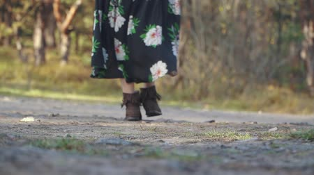 řev : Woman in a long dress with flowers walk on the ground road. Girl walking outdoors.