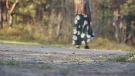 kükreme : Girl in a long dress with flowers walk on the ground road. Woman walking outdoors.