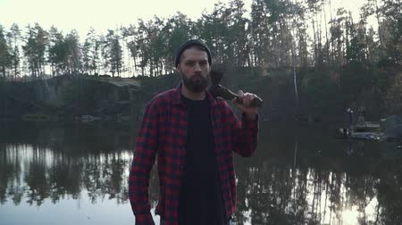тройник : Bearded young man with an ax on the shoulder. Brutal serious man with axe outdoors. Стоковые видеозаписи