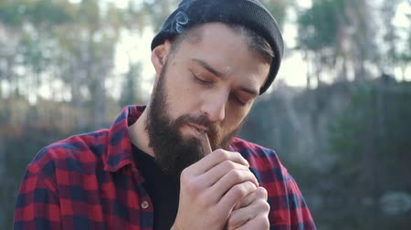good looking guy : Bearded guy smoking brown cigar in the forest near river. A man with a beard in a hat and a plaid shirt smokes a cigar in the autumn forest. Stock Footage