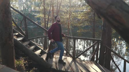 machado : Bearded guy with axe in hands walk by wooden stairs near amazing forest with lake. Young bearded man with an axe outdoors.