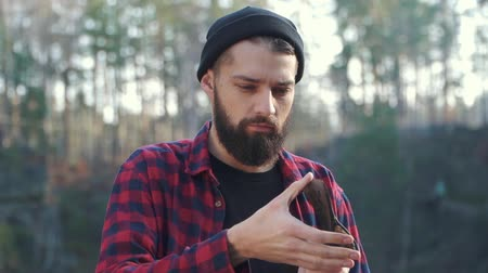 насилие : Brutal serious guy with ax outdoors. Bearded man stay with an axe in his hand in the forest.