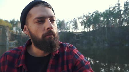 smoke kills : Portrait of a bearded guy sitting in the forest near river and smoking brown cigar. Brutal man with a black beard in a plaid shirt and blue jeans smoking a cigar outdoors.