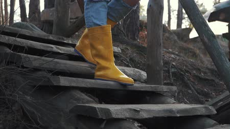 handrails : Human legs in yellow rubber boots and blue jeans walk down on the wooden stairs outdoors. Feet in rubber boots coming down a wooden staircase in the forest.
