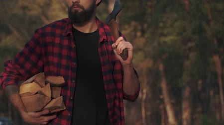 hatchet : Bearded guy walk in the forest with chopped logs in one hand and axe in his shoulder. Forester carries firewood. Slow motion.