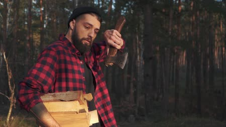hatchet : Bearded guy walk in the forest with chopped logs in one hand and axe in his shoulder. Forester carries firewood. The woodsman wipes his sweat with a hand. Slow motion. Stock Footage