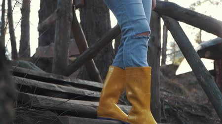 párat se : Human legs in yellow rubber boots walk down on the wooden stairs in the forest. Feet in rubber boots coming down a wooden staircase outdoors. Dostupné videozáznamy