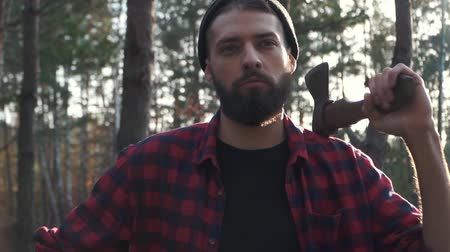топор : Portrait of a bearded man in a plaid shirt standing with an ax in his hand in the forest.. Brutal serious guy with ax outdoors. Slow motion.
