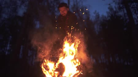 топор : Bearded man chopping a burning log at night in the forest. Brutal guy with ax outdoors. Стоковые видеозаписи