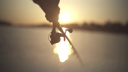 fishing pole : Male hand holds fishing rod on the background of the river during sunset close-up. Fisherman holds a fishing rod against the sunset. Sunlight through a fishing rod. River fishing.