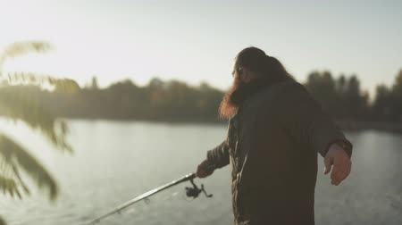 フィッシャー : Fisherman throws the rod into the river. Bearded fisher fishing with fishing rod standing on the bank of the river. River fishing.