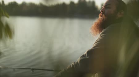 fishing pole : Fisherman with long beard catches fish sitting on the river bank. Fisher wave his hand greetiings his friend. River fishing. Stock Footage