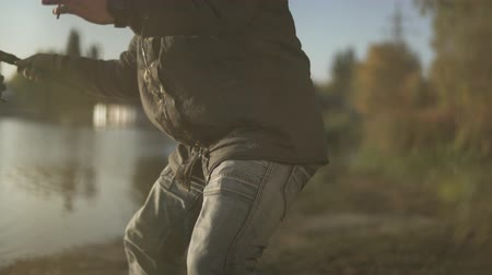 fly fishing : Bearded fisherman fishing on the lake. Fisher smokes sigarrette on fishing. Stock Footage
