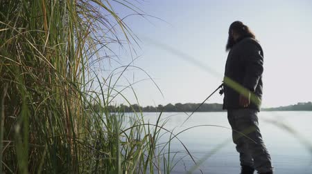 fishing pole : Bearded man is fishing on the river bank. Fisherman is trying to get fish, but it escapes. River fishing.