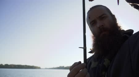 habilidade : Fisherman puts a worm on the hook and points on it. Portrait of adult man with beard who is fishing. River fishing. Fishing on the river.