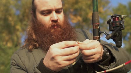 fishing pole : Fisherman puts a worm on the hook and points on it. Portrait of adult man with beard putting bailt on the hook. Fishing with live bait. Fishing on the river. Stock Footage
