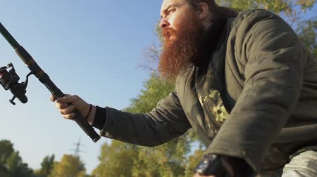 fly fishing : Fisher with long beard fishing on the river bank. Fisherman emotionally waiting for the fish. River fishing. Stock Footage