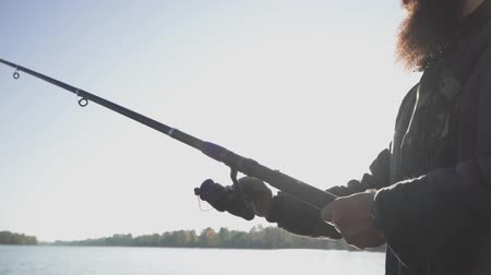 fishing pole : Bearded fisherman fishing with a fishing rod on the river. River fishing. Slow motion.