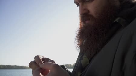 outdoor hobby : Fisherman puts a worm on the hook. Portrait of adult man with beard putting bailt on the hook. Fishing with live bait. Fishing on the river. Stock Footage