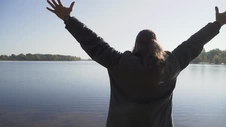 üdvözlet : The man with long hair raises hands to the sky standing on the river bank. Bearded man with long hair in a pigtail is enjoying the sunshine outdoors. Stock mozgókép