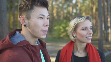 příloha : Portrait of smilling interracial couple outdoors. Asian guy and caucasian girl on a date. Beautiful interracial couple in casual wear is relaxing in nature and spending time together. Dostupné videozáznamy