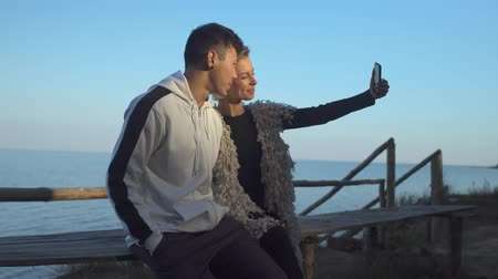 připevnění : Interracial young couple in love makes selfie sitting on a wooden bench in the sunshine on the background of a lake. Asian guy kisses his caucasian girlfriend on a date outdoors. Dostupné videozáznamy