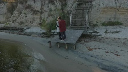 připevnění : Aerial view of a young couple tenderly embracing at the river. An attractive couple standing on a wooden platform on the background of a wooden ladder. Shooting from the drone. Slow motion.