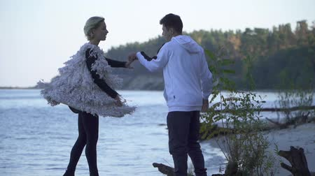 příloha : Teenagers in casual wear dancing on the sandy river bank. Interracial couple dancing in free style outdoors. Asian guy and caucasian girl dancing contemporary dance. Slow motion.