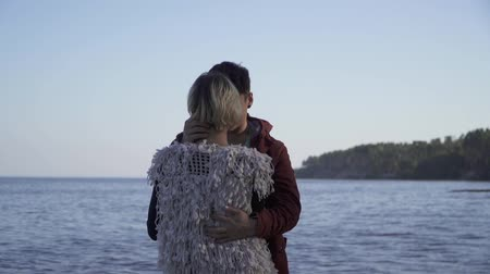 příloha : The guy hugs a girl on the background of the water surface. Young people in casual wear. Full height, the girl stands with his back to the camera, the guy hugs the girl, no faces are visible. Dostupné videozáznamy