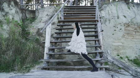 příloha : Pretty young caucasian woman in casual dancing contemporary dance outdoors. Flexible girl in tight leggings dancing on a wooden platform on the background of wooden stairs. Dostupné videozáznamy