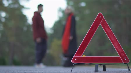 плохо : Two people swear on a background of warning triangle. Silhouette of swearing couple. Focus on car sign.