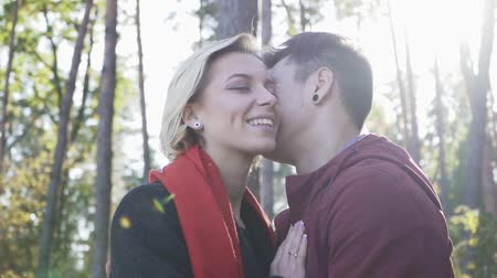 příloha : Young smiling couple in love kissing on a background of pine trees and sunset light. Multi ethnic couple in love. Dostupné videozáznamy