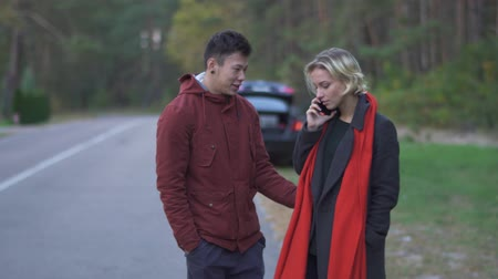 stories : A young couple standing on background of a car parked on the side of the road. Beautiful girl with blond hair is talking on the cell phone while standing near her husband outdoors. Relationship of interracial couple. Accidents on the road. Stock Footage