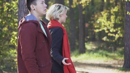 příloha : A beautiful young playful girl with blond hair in a coat and a red scarf runs away from her boyfriend in the forest. The guy runs after the girl through the pine forest in the sun. Leisure of a young multi ethnic couple outdoors. Slow motion.