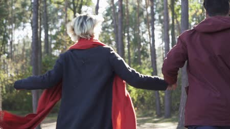 приложение : Young couple holds hands and runs in the pine forest in the rays of the sun. Guy and girl in casual wear spend leisure time in the sunshine. Nice couple in love outdoors. Slow motion.