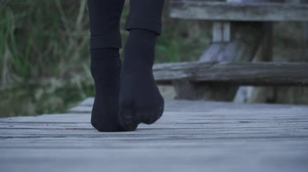 발목 : Close up legs with clenched toes walking on a wooden surface outdoors. 무비클립