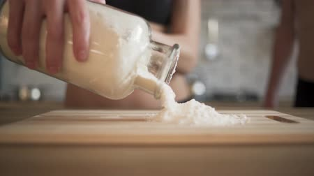 poured out : Girl pours the flour from the jar on a cutting board lying on the table. Workplace.