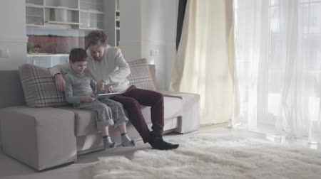 домашнее задание : Dad and son using digital tablet sitting on the couch in large living room. Happy family spend time together. Relationship between parent and kid. Dad teaches his child. Father-son relationship.