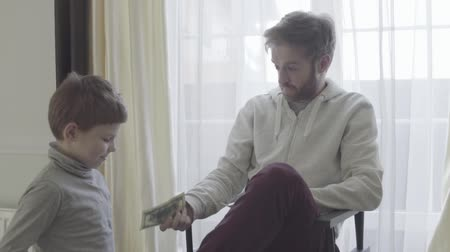 bolso : Father agrees with the child. Father gives to his little son pocket money. Father-son relationship. Stock Footage